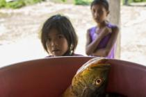 Two indigenous girls watch a lunch is prepared, Mangalito village, Bolivia