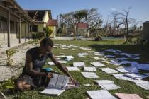 A teacher dries books in the sun after Cyclone Pam in Vanuatu