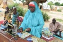 A displaced woman works with her sewing machine in an IDP camp in Damboa, Borno state, Nigeria. Photo: Tom Saater/Oxfam