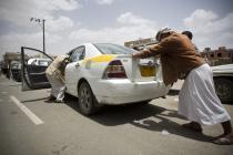 Des Yéménites poussent une voiture en panne d'essence vers une station-service à Sanaa, au Yémen. Photo : Abo Haitham