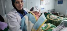 A doctor holds a new born baby in Za'atari camp, Jordan