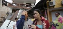 Une femme pleure devant des bâtiments effondrés, Equateur.