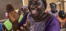 Isatu Kamara, 40, leads oxfam volunteers and the community in a song to thank Oxfam for their intervention during the Ebola outbreak. Sierra Leone, April 2015. Photo:Tommy Trenchard/Oxfam