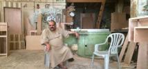Anwar sits in his furniture workshop in Gaza. Photo: Sami Alhaw/Oxfam
