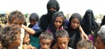 A mother and her children stand in the camp where they now live,  Bani Hassan, Yemen