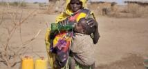 A mother gives her son a drink of water from an Oxfam tank in Ethiopia