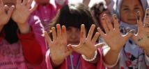 Syrian refugee children in Za'atari camp make the dove symbol of peace