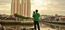 Looking at the future: a father holds his daughter as he stands on a site where residents have recently been evicted from nearby luxury apartments in North Jakarta. Photo: Tiara Audina/Antropologi UI