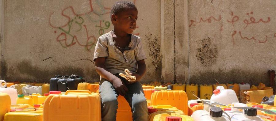 Un niño come el pan que le han dado en una panadería cercana mientras espera para recibir agua.