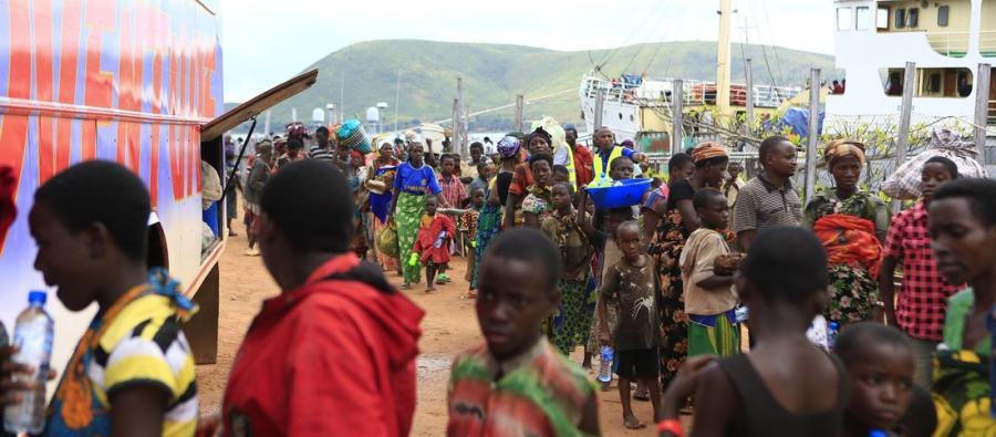 Burundian refugees boarding a bus to Lake Tanganyika Stadium