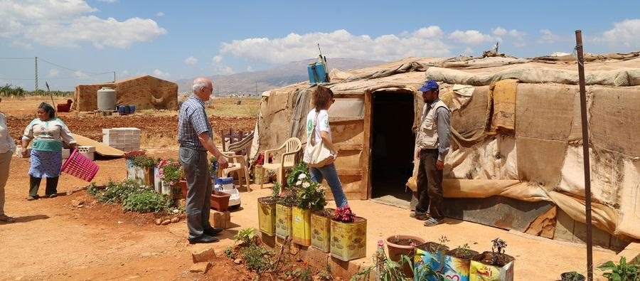 A refugee family stand outside their temporary home in an informal settlement, Bekaa Valley, Lebanon