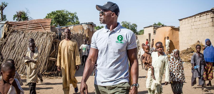 Djimon Hounsou camina por una calle de Jakana, Nigeria, que conduce a uno de los campos para personas desplazadas.