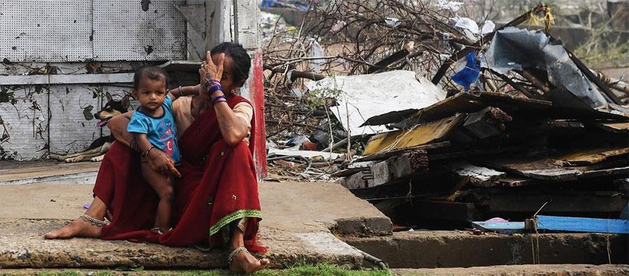 Una mujer india está sentada con su hijo junto a edificios completamente destruidos en Puri, en el estado indio oriental de Odisha, el 4 de mayo de 2019, después de que el ciclón Fani barriera la zona. Foto: DIBYANGSHU SARKAR / AFP / Getty Images