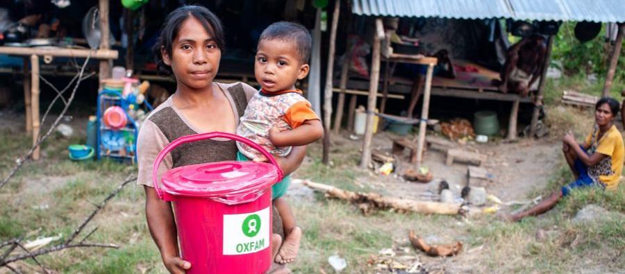 Afrianti et son fils devant un point de distribution de kits d'hygiène installé par Oxfam près de Palu. Le séisme a entraîné le déplacement de 88 000 personnes vers des sites non pourvus d'installations sanitaires ou d'accès à l'eau. Photo: H.Hafid/Oxfam