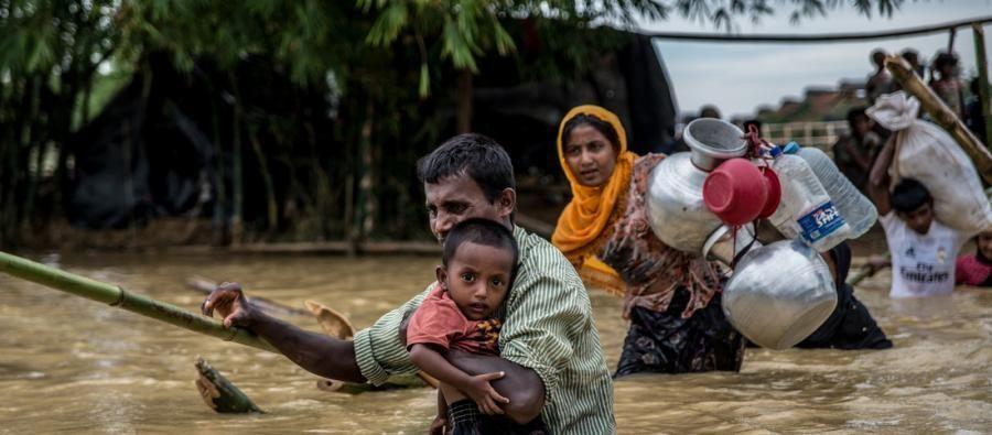 Un homme porte son fils alors qu'il traverse un pont cassé aux abords du camp de Balhukali, au Bangladesh. Des pluies intenses ont inondé les zones où les réfugiés avaient installé des abris temporaires. Photo: Aurélie Marrier d'Unienville