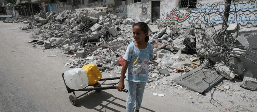 Una niña transporta agua para su familia rodeada de escombros y edificios destruidos, Gaza.