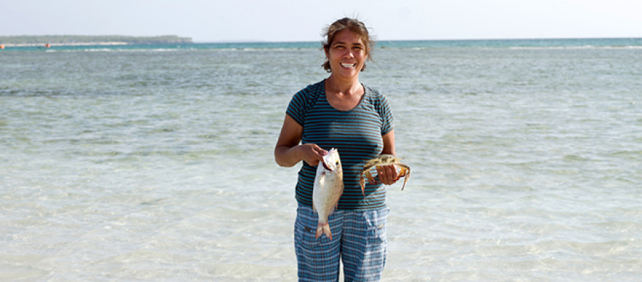 Woman holding a fish by the sea, Philippines