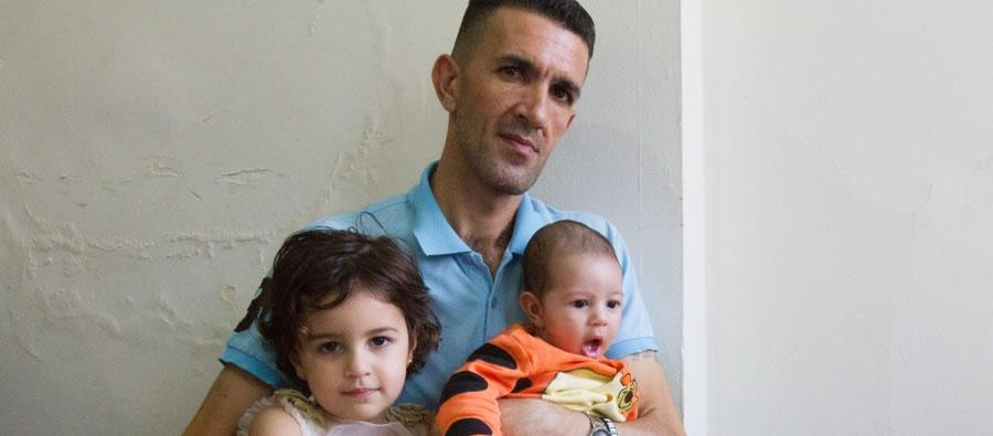 Ahmed Abizaid, with two of his five children, is working to build a new life for himself and his family in a Chicago suburb after fleeing the violence in Syria. Photo credit: Coco McCabe