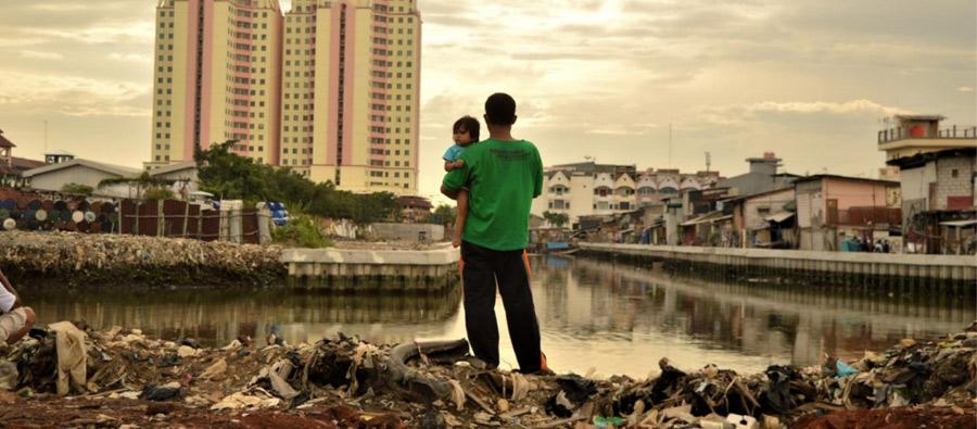 Looking at the future: a father holds his daughter as he stands on a site where residents have recently been evicted from nearby luxury apartments in North Jakarta. Photo: Tiara Audina/Antropology UI