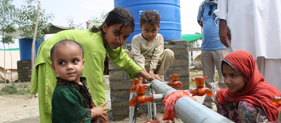 Children washing their plates at an Oxfam water point, Swat valley, Pakistan