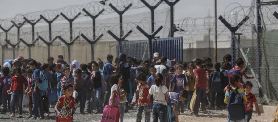 Des enfants syriens se regroupent dans le camp de réfugiés de Zaatari, en Jordanie, devant une barrière et des barbelés.