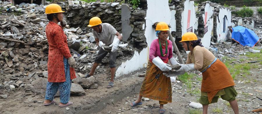 Fifty-one-year-old Dil Maya Sunar (second from right) hands a stone from a collapsed school block to her colleague at Golma Devi School in Timbu of Sindhupalchowk district. Photo: Rakesh Tuladhar/Oxfam