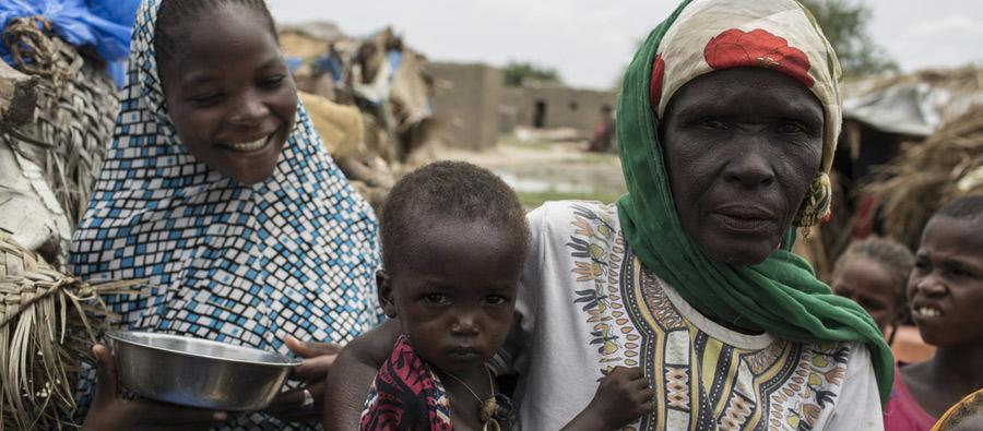 Amina*, 55, a mother of 12, stands with her children outside their hut in the village of Toumour in north eastern Niger, on September 6, 2016. Photo: Pablo Tosco/Oxfam