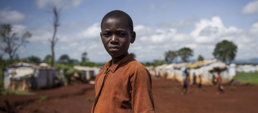 """Un jeune réfugié du Burundi devant le camp de Nyarugusu, en Tanzanie, le 26 mars 2016. Selon le HCR, Nyarugusu est """"l'un des camps les plus grands et les plus surpeuplés au monde"""". Il abrite actuellement plus de 140 000 réfugiés."""