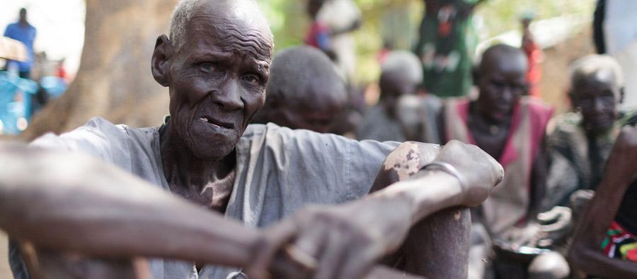 Majok esperando la distribución de alimentos del Programa Mundial de Alimentos en Nyal. Ayudado por sus familiares, tuvo que caminar durante hora y media desde su casa para estar presente físicamente en el registro. Foto: Bruno Bierrenbach Feder/Oxfam
