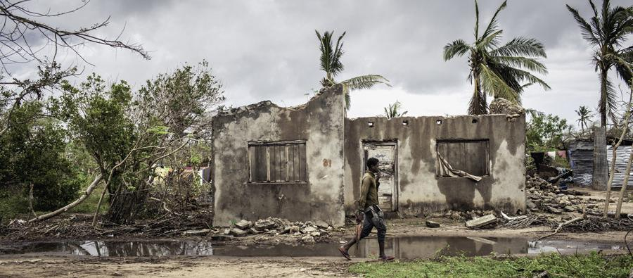 A young man passes by a destroyed house in Ibo Island, one of the most affected areas by Cyclone Kenneth in April 2019.