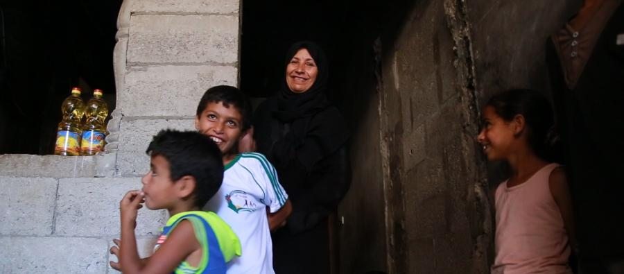 A beneficiary of an Oxfam food voucher system stands outside her home, Gaza.