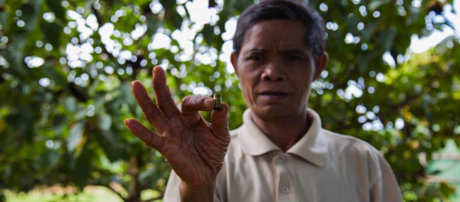 Sal Hnok holds a shell casing from a bullet fired at him when he insisted workers stop clear cutting the forest near his village in northern Cambodia