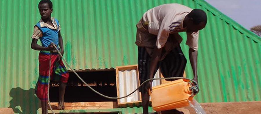 Abdi Ahmed Jamaa with one of his children fetching water from a rehabilitated water cistern (barkad). Photo TARDO/Oxfam