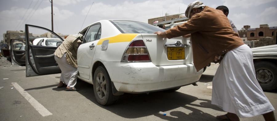 Yemeníes ayudan a empujar un coche en una estación de gasolina durante la escasez de combustible en Sanaa, Yemen. Foto: Abo Haitham