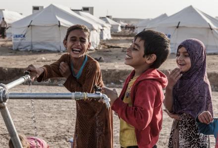 Des enfants remplissent des bouteilles d'eau à une rampe de distribution dans le camp de Hassansham. Oxfam y a installé des réservoirs d'eau potable et assure l'entretien des sanitaires. Photo: Tegid Cartwright/Oxfam