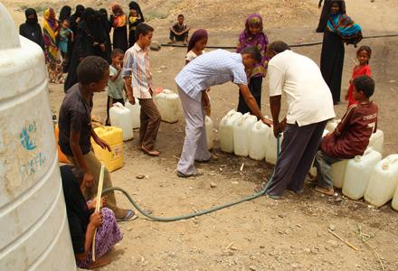 Yemen: People wait their turn to take share of the water for their families - Oxfam has provided water tanks and clean drinking water for the displaced.