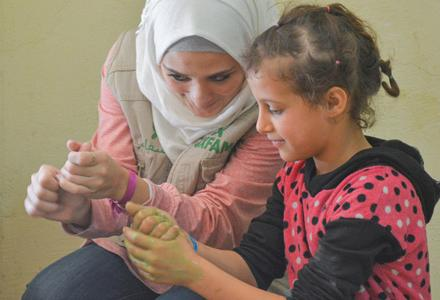 Sana, an Oxfam volunteer in Aleppo, shows children from Aleppo how to wash their hands properly. Credit: Islam Mardini/Oxfam