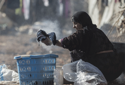 Basterna, 40, from Raqqa in Syria washes clothes by hand at an informal settlement for Syrian refugees near the town of Baalbek in Lebanon's Bekaa Valley, on January 26, 2016. Credit:Sam Tarling