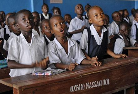 (Left to right): Emanuel Kun (7), Nush Gunror (5) and Kumba Lamie (8) during their 'numbers and letters' class (pre-primary) at N. V. Massaquoi School, West Point, Monrovia, Liberia. Photo credit: Aubrey Wade/Oxfam