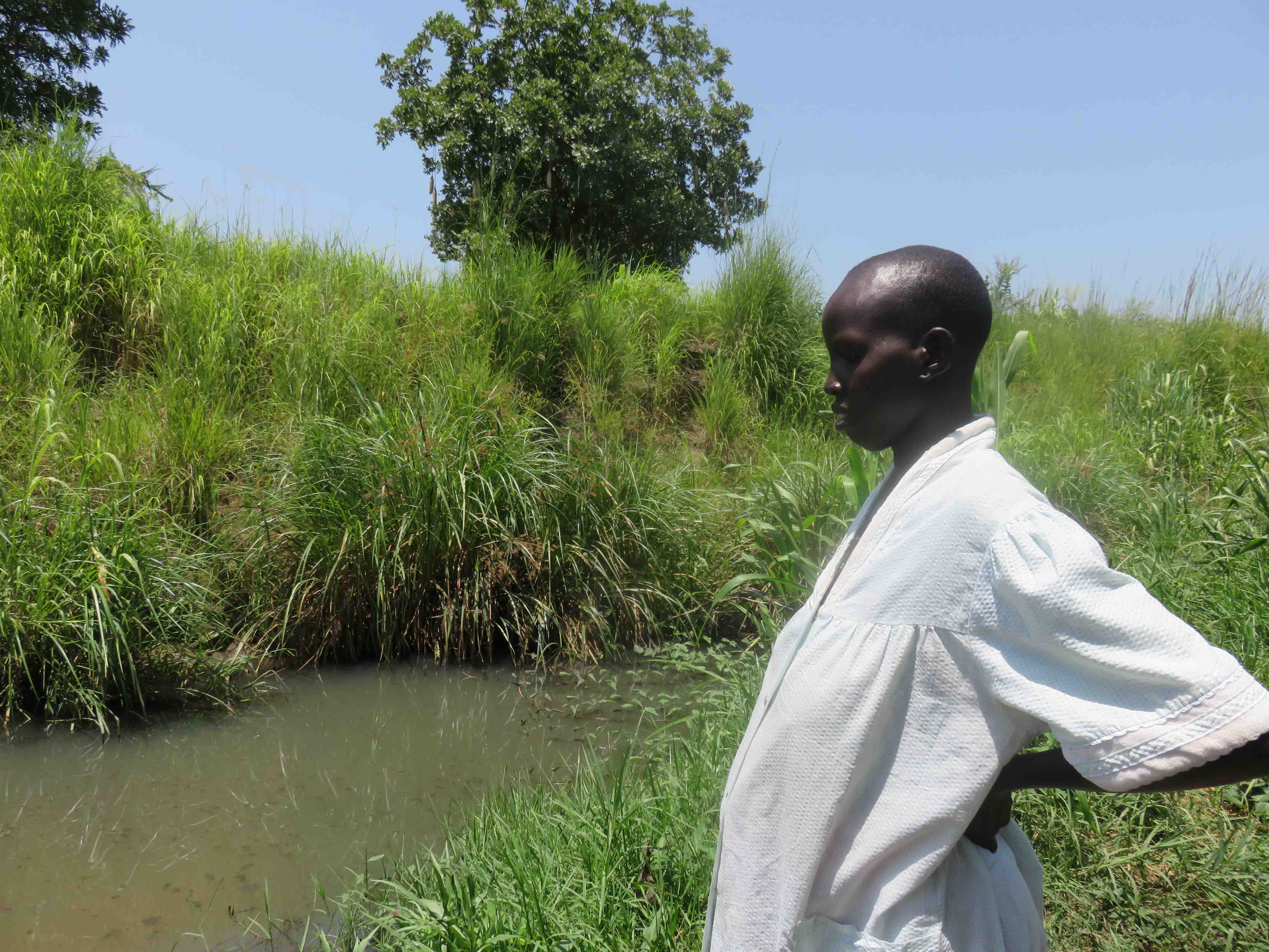 A woman stands by the village stream in Juba, South Sudan, where drinking water is collected
