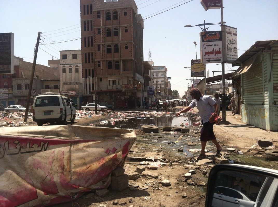 A man cautiously crosses a street covered with rubble, water, and garbage.